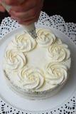 Las mujeres dan el adornamiento de la torta con un bolso de los pasteles con la crema blanca Imágenes de archivo libres de regalías