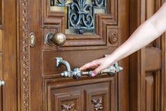 Las mujeres dan el botón de puerta abierta o la apertura de la puerta Fotos de archivo libres de regalías