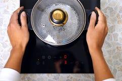Las mujeres dan la cacerola puesta en cocina moderna con la estufa de la inducción imagenes de archivo