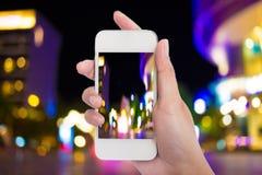 Las mujeres dan llevar a cabo la luz elegante móvil en blanco del teléfono y de la noche de la ciudad Imagen de archivo libre de regalías