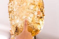Las mujeres dan poner la hoja de oro sobre la estatua de Buda para dorar Fotografía de archivo libre de regalías