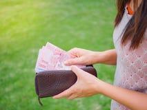 Las mujeres dan sacar a dinero el baht tailandés de la cartera foto de archivo libre de regalías