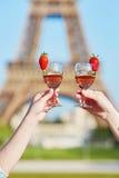 Las mujeres dan sostener dos vidrios de vino con la torre Eiffel en el fondo Foto de archivo libre de regalías