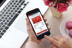 Las mujeres dan sostener el teléfono con compras en línea del app cerca del ordenador portátil imágenes de archivo libres de regalías