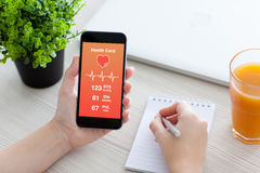 Las mujeres dan sostener el teléfono con el app para la supervisión de la tarjeta de salud Fotos de archivo libres de regalías