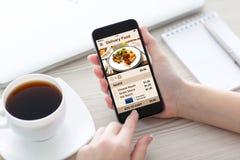 Las mujeres dan sostener el teléfono con la comida de la entrega del app en la pantalla fotos de archivo libres de regalías