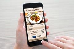 Las mujeres dan sostener el teléfono con la comida de la entrega del app en la pantalla foto de archivo