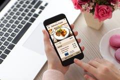 Las mujeres dan sostener el teléfono con la comida de la entrega del app en la pantalla foto de archivo libre de regalías