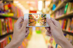 Las mujeres dan sostener el teléfono elegante móvil en blanco en librería encendido ella Imágenes de archivo libres de regalías