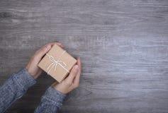 Las mujeres dan sostener la caja de regalo en de madera por la Navidad y el Año Nuevo Imagenes de archivo