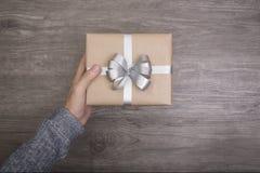 Las mujeres dan sostener la caja de regalo en de madera por la Navidad y el Año Nuevo Fotografía de archivo libre de regalías