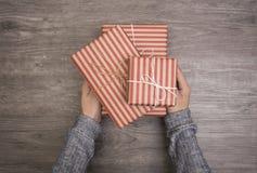 Las mujeres dan sostener la caja de regalo roja en de madera para la Navidad Foto de archivo libre de regalías