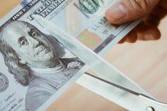 Las mujeres dan sostener las tijeras que cortan billetes de banco del dólar de EE. UU., cortaron el brote Imagenes de archivo