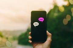 Las mujeres dan usando smartphone que mecanografían, charlando la conversación en iconos de la caja de la charla surgen imagen de archivo libre de regalías