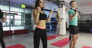Las mujeres de la aptitud están entrenando con la barra de cuerpo en el gimnasio almacen de video