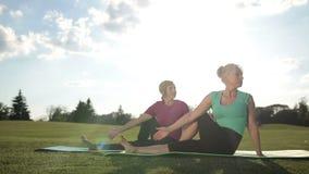 Las mujeres de la aptitud que hacen la pierna de los pilates estiran ejercicio almacen de metraje de vídeo