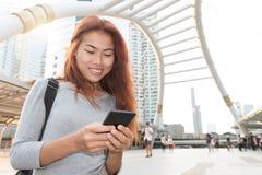 Las mujeres de la belleza sonríen tipo móvil mensaje del smartphone del uso foto de archivo libre de regalías