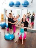 Las mujeres de los pilates de los aeróbicos embroman al amaestrador personal de las muchachas Fotografía de archivo