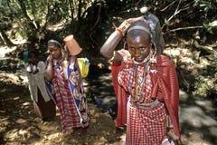 Las mujeres de Maasai han traído el agua en pequeña corriente Imagen de archivo libre de regalías