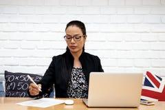 Las mujeres de negocios asiáticas hermosas están trabajando con el ordenador portátil en café Imagen de archivo