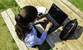Las mujeres de negocios con el ordenador portátil, sentándose en el jardín y hacen mucho, Fotografía de archivo