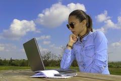 Las mujeres de negocios con el ordenador portátil, sentándose en el jardín y hacen mucho, Imagen de archivo libre de regalías