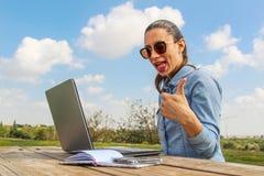 Las mujeres de negocios con el ordenador portátil, sentándose en el jardín y hacen mucho Fotografía de archivo libre de regalías