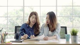 Las mujeres de negocios creativas asiáticas que se inspiran para crean el plan de márketing en oficina, funcionamiento femenino j almacen de video