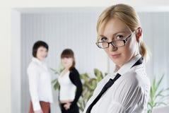 La mujer de negocios joven en la oficina con los colegas Foto de archivo