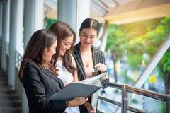 Las mujeres de negocios miran el informe y hablar con cada uno otros, concepto del negocio, concepto de la belleza imagenes de archivo