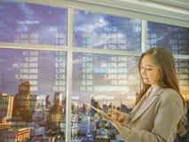 Las mujeres de negocios modernas miran cosa de la tableta sobre mercado de acción foto de archivo