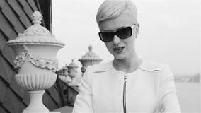 Las mujeres de negocios rubias atractivas hermosas que llevan la reunión que espera de la chaqueta blanca de las gafas de sol hab almacen de video