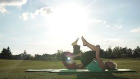 Las mujeres de Pilates que hacen el balanceo les gusta un ejercicio de la bola metrajes