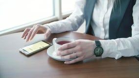 Las mujeres de un negocios jovenes que trabajan en whith del café llaman por teléfono metrajes