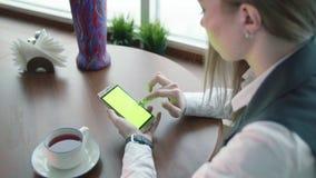 Las mujeres de un negocios jovenes que trabajan en whith del café llaman por teléfono a la pantalla verde almacen de video
