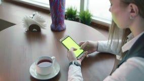 Las mujeres de un negocios jovenes que trabajan en whith del café llaman por teléfono a la pantalla verde almacen de metraje de vídeo