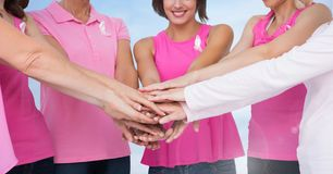 Las mujeres del cáncer de pecho que llevan a cabo las manos con el cielo se nublan el fondo fotos de archivo