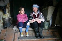 Las mujeres del granjero sientan en pasos la entrada a la casa de campo Imágenes de archivo libres de regalías