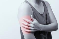 Las mujeres del primer arman y llevan a hombros dolor/lesión con puntos culminantes rojos en área del dolor con los fondos blanco Fotos de archivo