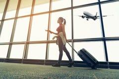 Las mujeres del viajero planean y la mochila ve el aeroplano en la ventana de cristal del aeropuerto, el bolso turístico del cont fotos de archivo libres de regalías