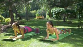 Las mujeres deportivas de la aptitud que hacen el tablón ejercitan en parque almacen de video