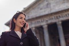 Las mujeres ejecutivas encantadoras jovenes hablan por un pho de la célula del teléfono móvil Imágenes de archivo libres de regalías