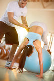 Las mujeres ejercitan en la bola en el gimnasio con la ayuda de instructo foto de archivo