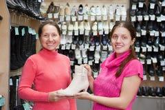 Las mujeres eligen los zapatos en el departamento de zapatos Fotos de archivo libres de regalías