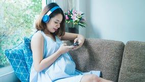 Las mujeres embarazadas están escuchando la música en el sofá y están jugando m imagenes de archivo