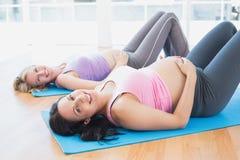 Las mujeres embarazadas sonrientes en yoga clasifican la mentira en las esteras Foto de archivo libre de regalías