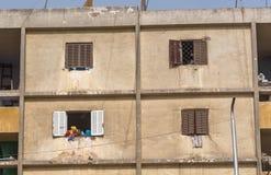 Las mujeres en bufandas principales coloridas ríen hacia fuera la ventana del apartamento del cemento mientras que un pequeño muc Fotografía de archivo