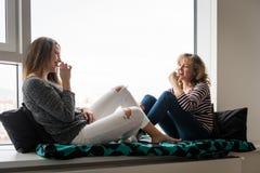 Las mujeres en casa arrancan con los dientes la rebanada de la barra de chocolate Imagen de archivo libre de regalías