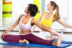 Las mujeres en el gimnasio que hace yoga ejercitan para la aptitud Foto de archivo libre de regalías