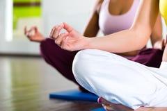 Las mujeres en el gimnasio que hace yoga ejercitan para la aptitud fotos de archivo libres de regalías